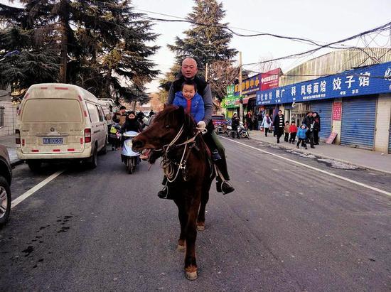 父子俩骑马走过街道本报记者李小刚摄
