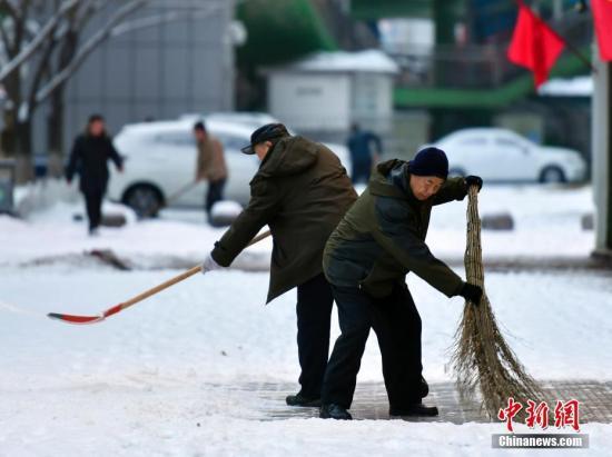 农历狗年正月初一,民众在乌鲁木齐街头清理人行道上的积雪。中新社记者 刘新 摄