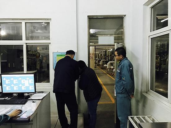 执法人员在仔细核对厂方投料记录。