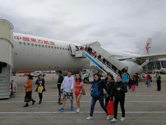 图为旅客回国后下飞机场景 东航供图