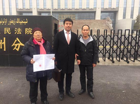 再审宣判后,周远(右),李璧贞(左)和律师在法院前合影。澎湃新闻记者 陈雷柱 图
