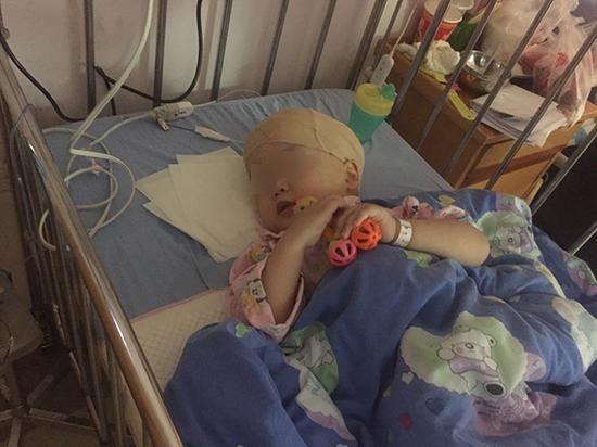 12月7日下午,做完外引流手术后,含含躺在病床上玩摇铃。澎湃新闻见习记者 李佳蔚 摄