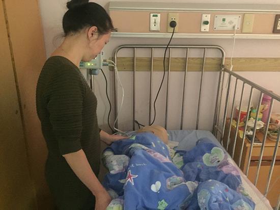 12月7日,郭银珍在病床前照顾儿子。澎湃新闻见习记者 李佳蔚 摄