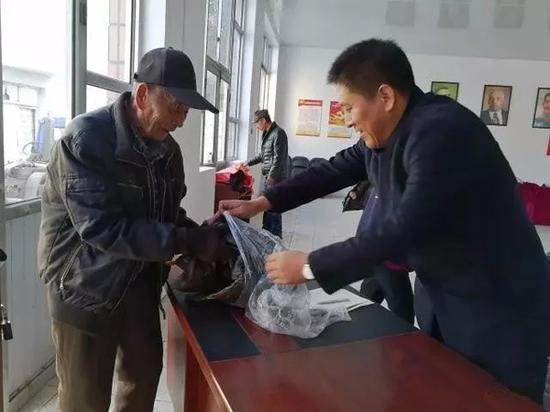 安新县安新镇大张庄村为全村老人及五保户免费发放羽绒服。