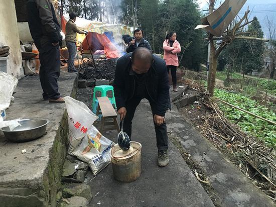 李明华的妹夫杨传玉(中)帮助李高愧喂牛喂猪。澎湃新闻记者 王鑫 摄