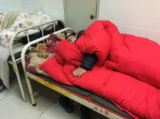 守在镇雄县人民医院的李高兵。澎湃新闻记者 王鑫 摄