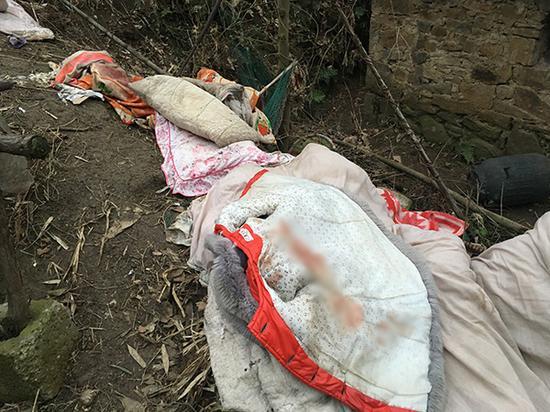 丢弃在房屋外的衣服和被子,上面的血迹十分明显。澎湃新闻记者 王鑫 摄