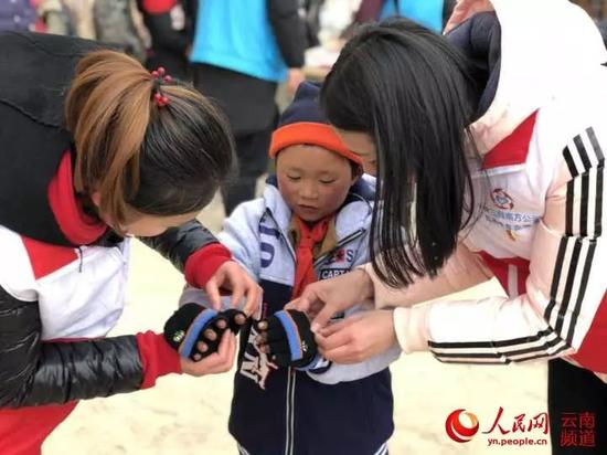 1月10日,中建三局志愿者在转山包小学为小满穿上棉衣、戴上手套。摄影:叶龙飞