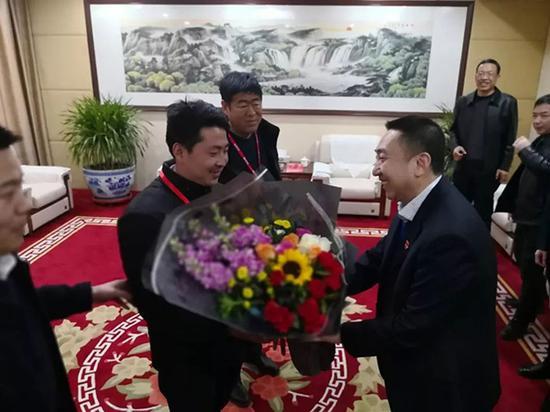 临猗县委书记于鹏飞(右三)将一捧鲜花送给李朋璇。