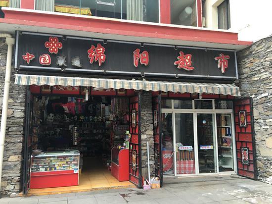 """周琴家开的""""绵阳超市""""距离九寨沟景区入口约800米,因游客还不多,她一个人就可照看这家超市。"""