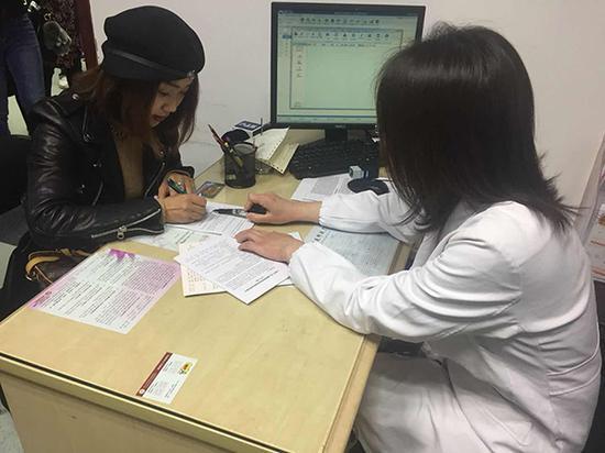 上海首位接种HPV四价疫苗的女性邱琼在接种前进行一次评估,签署接种知情同意书。 本文图片 澎湃新闻记者 陈斯斯
