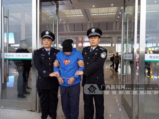 犯罪嫌疑人被押解出站。