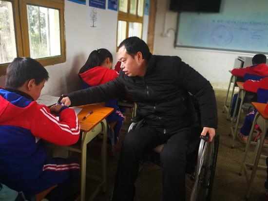 余国安在辅导学生。资料图片