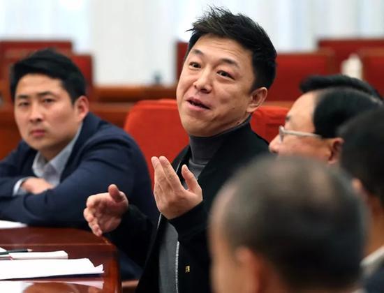 9人中演员黄渤发言,李朋璇(左)坐在他旁边。 中国政府网 图