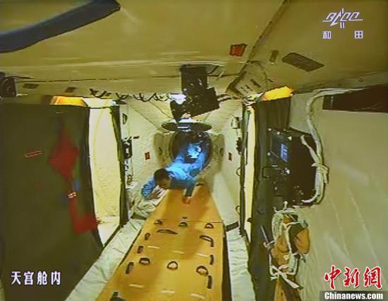图为在张晓光的协助下,聂海胜顺利开启并进入天宫一号舱门(资料图)。中新社发 秦宪安 摄