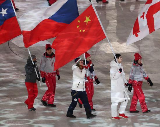 ▲2月25日,中国运动员武大靖(右二)手举中国国旗在闭幕式上入场。 图/新华社
