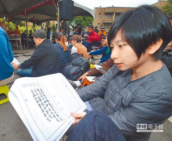 """反对""""劳基法""""再修,劳团与青年团体在Facebook成立""""过劳功德会""""粉丝页,3日在台当局""""行政院""""大门口前唱诵""""劳基法经""""表达不满。(图片来源:台湾《中时电子报》)"""