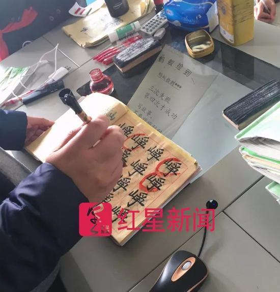 ▲王悦微在课堂上批改学生的作文和书法作业  图片来源:红星新闻