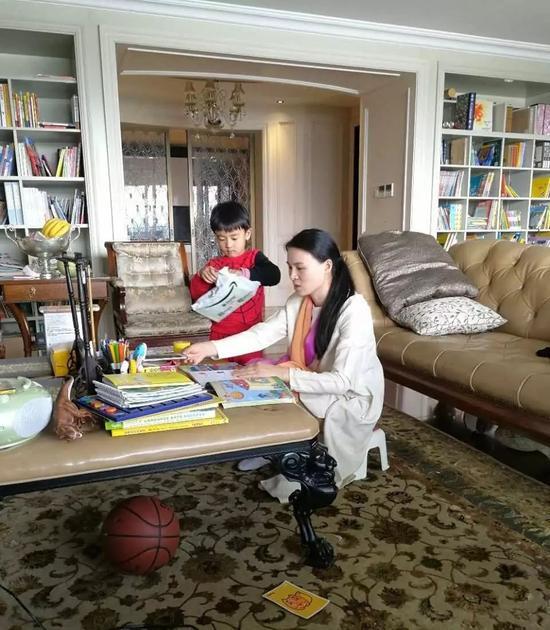 ▲朱小贞和小儿子在客厅里,背后书架为起火点。受访者供图