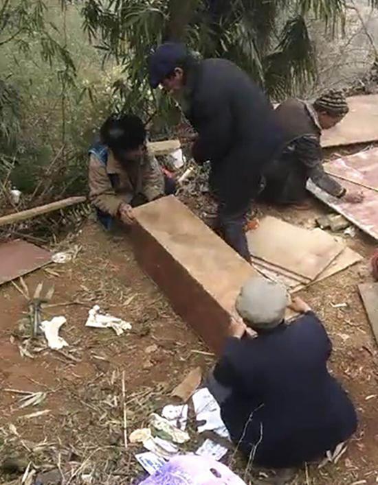 """出事后,亲戚邻居使用几年前建房剩下的木板做成""""棺材""""。"""