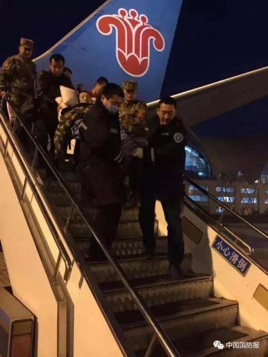 航班抵达乌鲁木齐机场,陈石被合力抬下飞机 图片来源:中国国防报