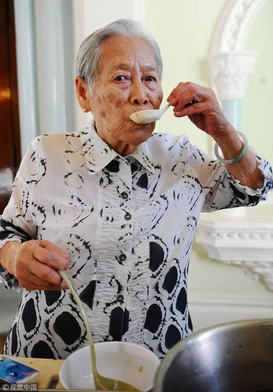 """▲2010年10月12日,香港大学,83岁的""""三嫂""""袁苏妹回到港大,为大学堂(港大的学生宿舍楼之一)的新生调制一道传统饮料——hall blood""""宿舍之血""""。三嫂在试口味。图/视觉中国"""