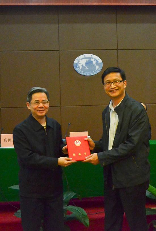 郑泽光(左)副部长向戚振宏(右)同志颁发任命书。