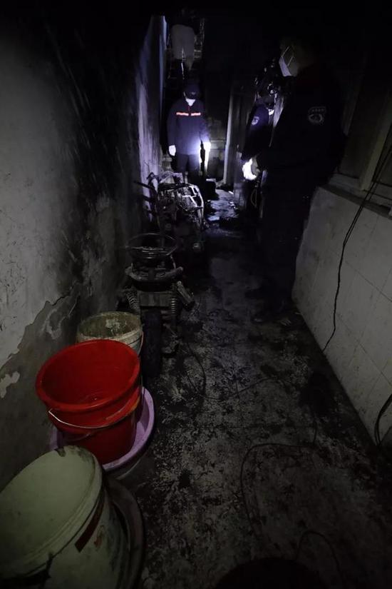 村民自救留下的水桶,摆放在起火电瓶车旁。