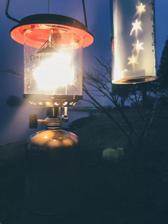 夜幕低垂,湖边雾气弥漫,燃气小灯发成的蓬蓬声让人温暖