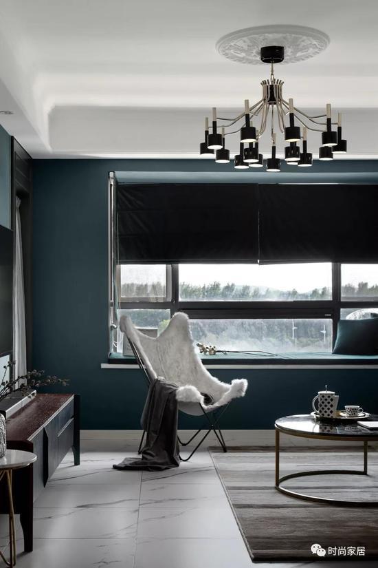 沙发背景是一款网红的乌云壁纸,灰色与墨绿色撞色更显时尚感。