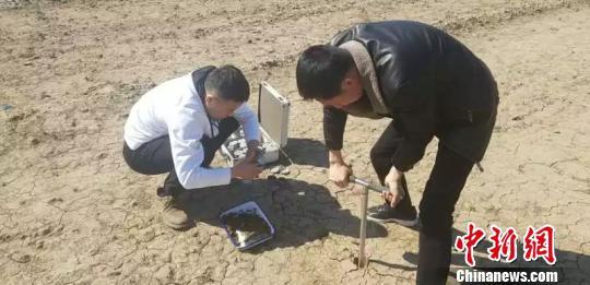 图为工作人员进行土地墒情检测。内蒙古农牧厅供图