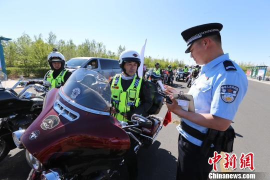图为边检民警为自驾游旅客办理通关手续。 李爱平 摄