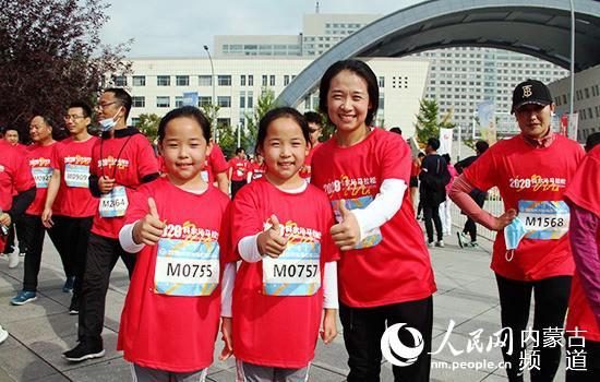 王建牵着双胞胎女儿参加马拉松,与记者分享完赛感受。张聿修 摄
