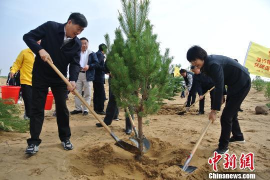 """图为在库布其沙漠上举行的""""大型义务植树活动""""现场。 李爱平 摄"""