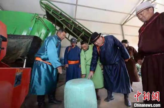 图为阿佈日米德(左一)为上门提问的牧民答疑。 齐波 摄