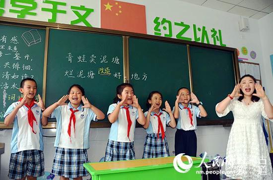 刘学敏与孩子们一起模拟书中的情景,特别的学习方式让孩子们很喜欢。王慧 摄