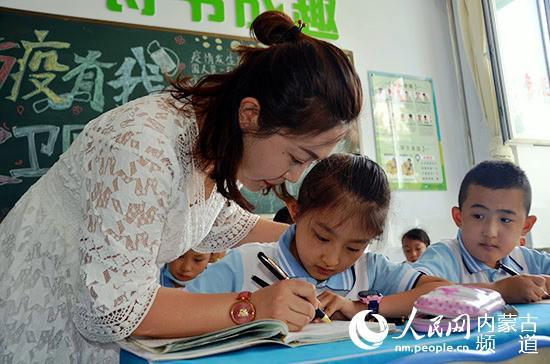 刘学敏辅导孩子写字。王慧 摄