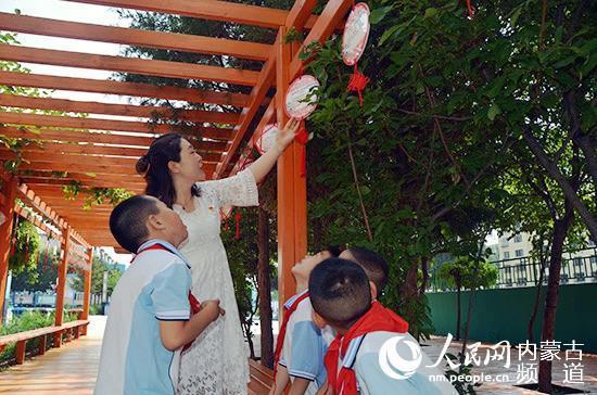 刘学敏在读书廊与孩子们阅读悬挂在廊道上的诗歌。王慧 摄
