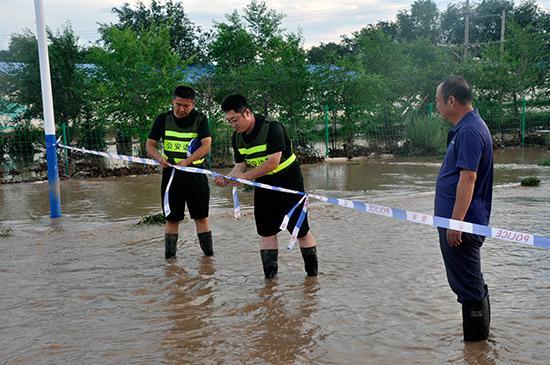 杜文伟(左二)同群众一起拉起警戒线隔离危险路段。
