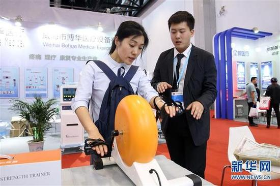 5月9日,一名参观者在博览会现场体验一台家用运动康复机。