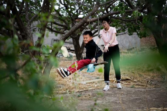 5月19日,王辅正和姐姐在双山村的院子里玩耍。