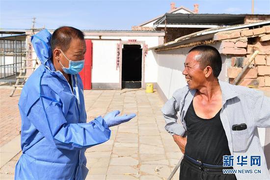 杭锦旗动物疫病预防控制中心的工作人员何荣利(左)来到杭锦旗巴拉贡镇朝凯村与村民王五牛交流(6月10日摄)。新华社记者 贝赫 摄