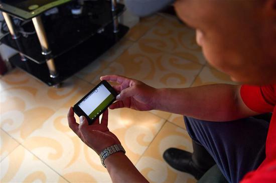 在内蒙古呼伦贝尔市新巴尔虎左旗新宝力格苏木贡诺尔嘎查,牧民苏尼尔在家中使用手机查看草场情况(7月15日摄)。 新华社记者 贝赫 摄