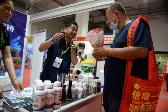 8月1日,商家向顾客介绍能改善土质的有机肥。