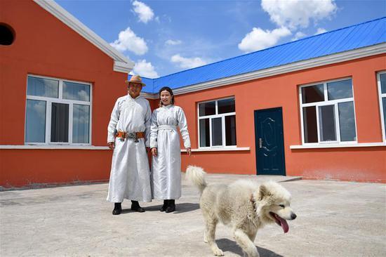 在内蒙古鄂温克族自治旗阿拉坦敖希特嘎查,牧民阿日斯楞和妻子特日格乐站在自家庭院中合影(7月15日摄)。新华社记者 贝赫 摄