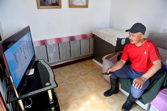 在距离新巴尔虎左旗70公里外的牧区深处,牧民苏尼尔在家中看电视(7月15日摄)。 新华社记者 贝赫 摄