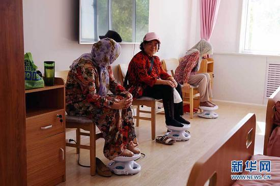 老人们在三顺店社区使用足底按摩器。新华网 石毅摄