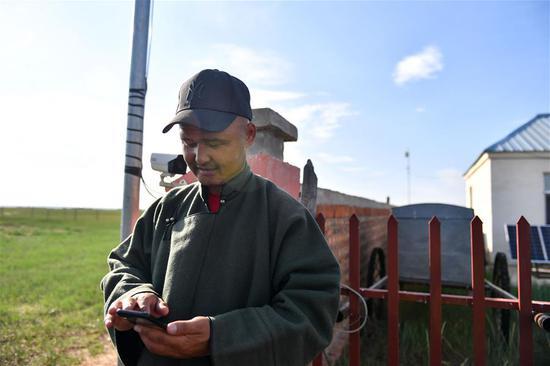 新巴尔虎左旗新宝力格苏木贡诺尔嘎查,牧民苏尼尔使用手机查看草场情况(7月15日摄)。 新华社记者 贝赫 摄