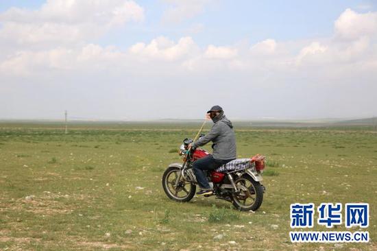 在草原上放马牧羊,很多时候要骑摩托。新华网 石毅摄