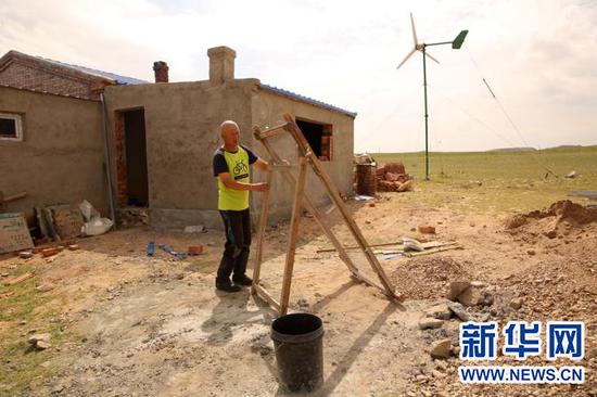 娜日娜丈夫盖哈玛在筛沙子,家里房子都是他自己盖起来的。新华网 石毅摄